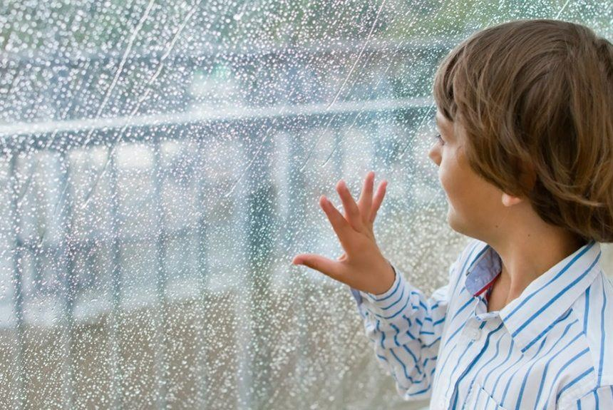 Little boy gazing out of a wet window