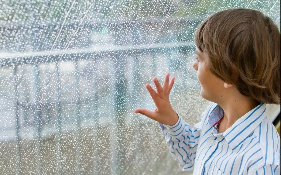 Little boy gazing out of a wet window